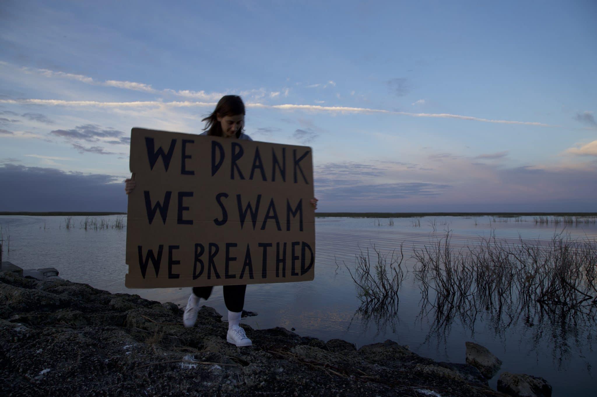 """Nastja med skiltet """"We drank we swam we breathed"""""""