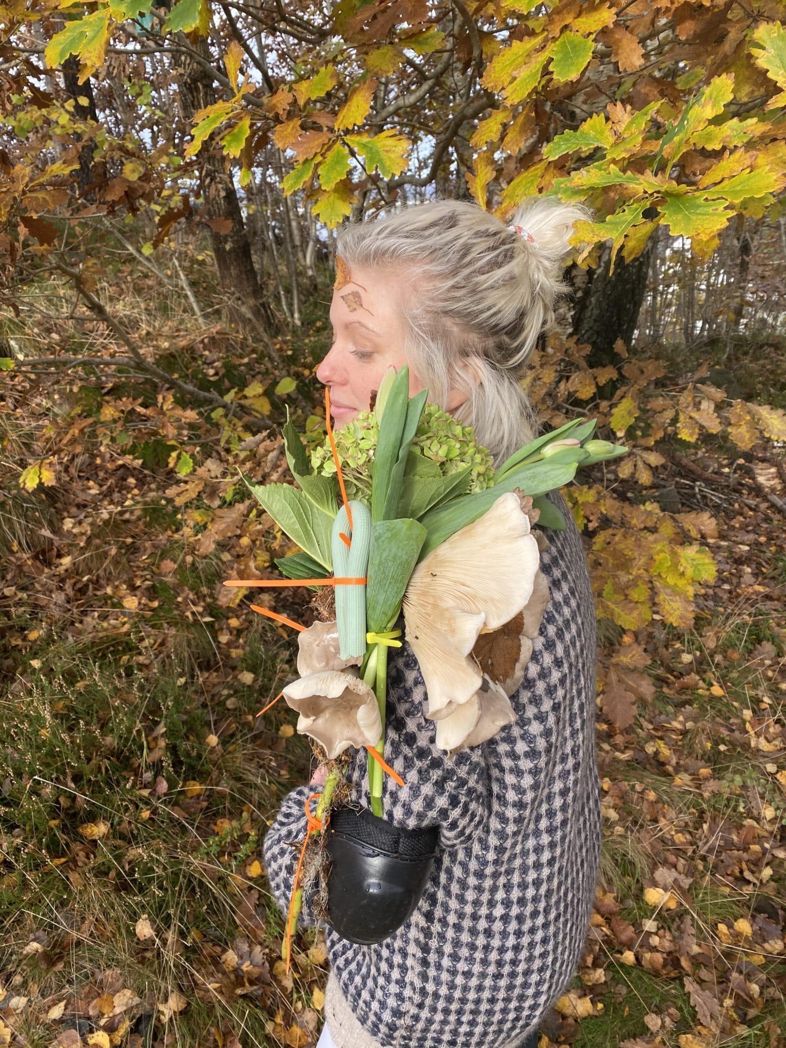 Pia Eikaas i skogen med kunstverk av blomster og søppel