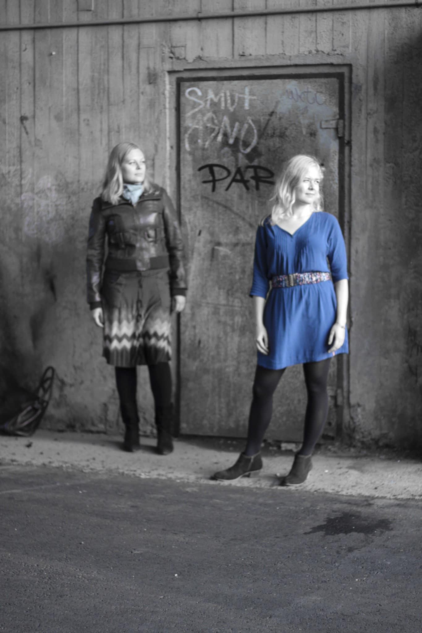 Kaksi naista seisoo betoniseinän edessä