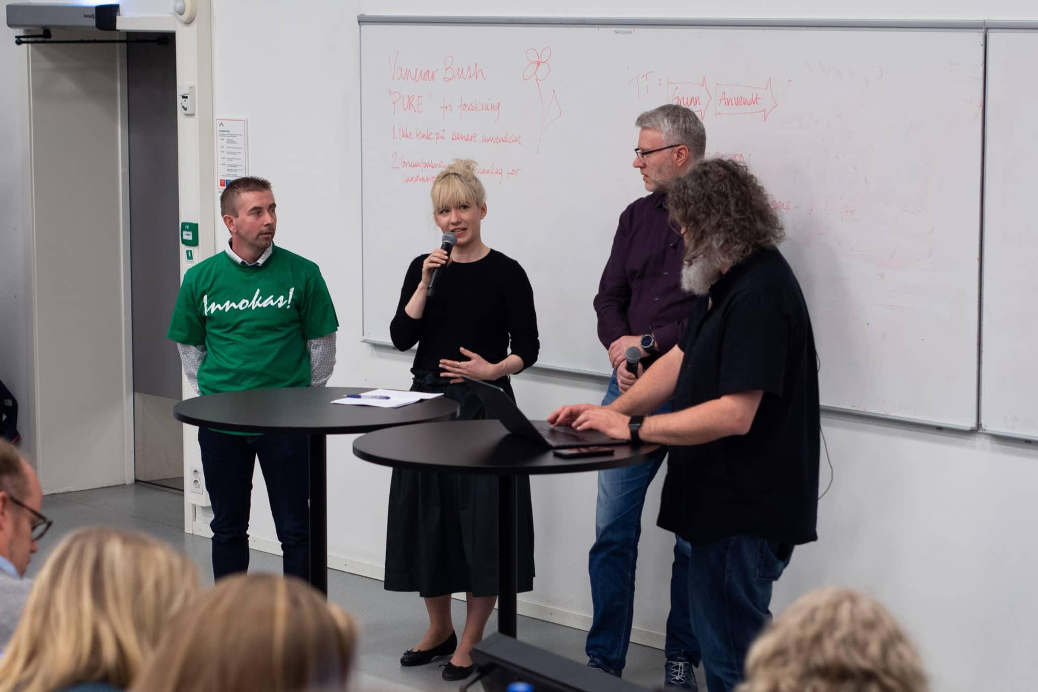 Neljä henkilöä puhuu yleisölle