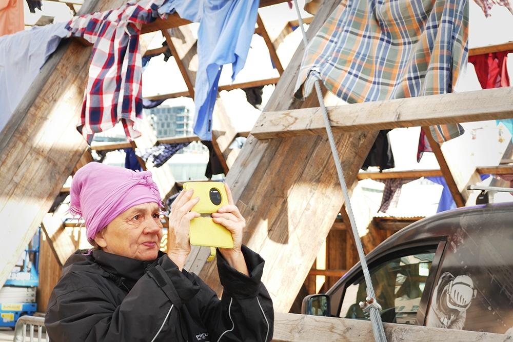 Nainen ottaa kuvaa rimoilla roikkuvista paidoista